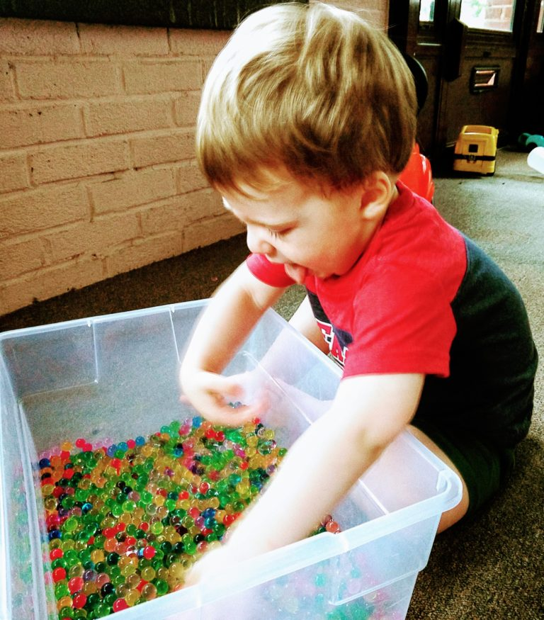 kid playing with water beads