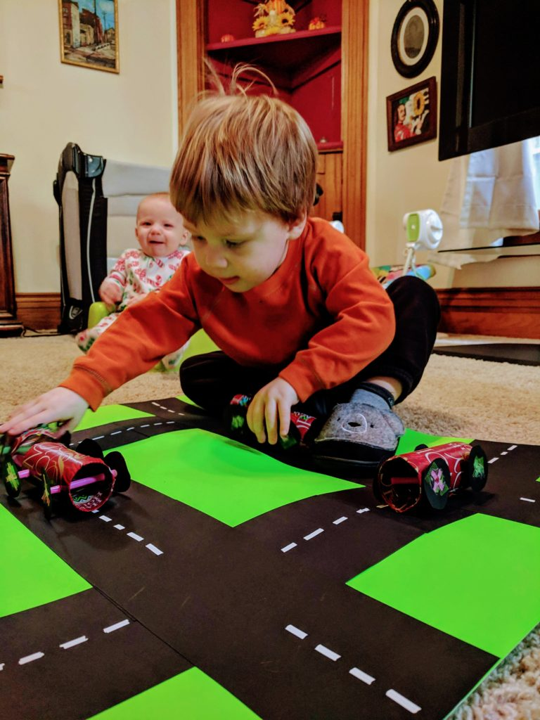 boy playing with paper roll craft cars