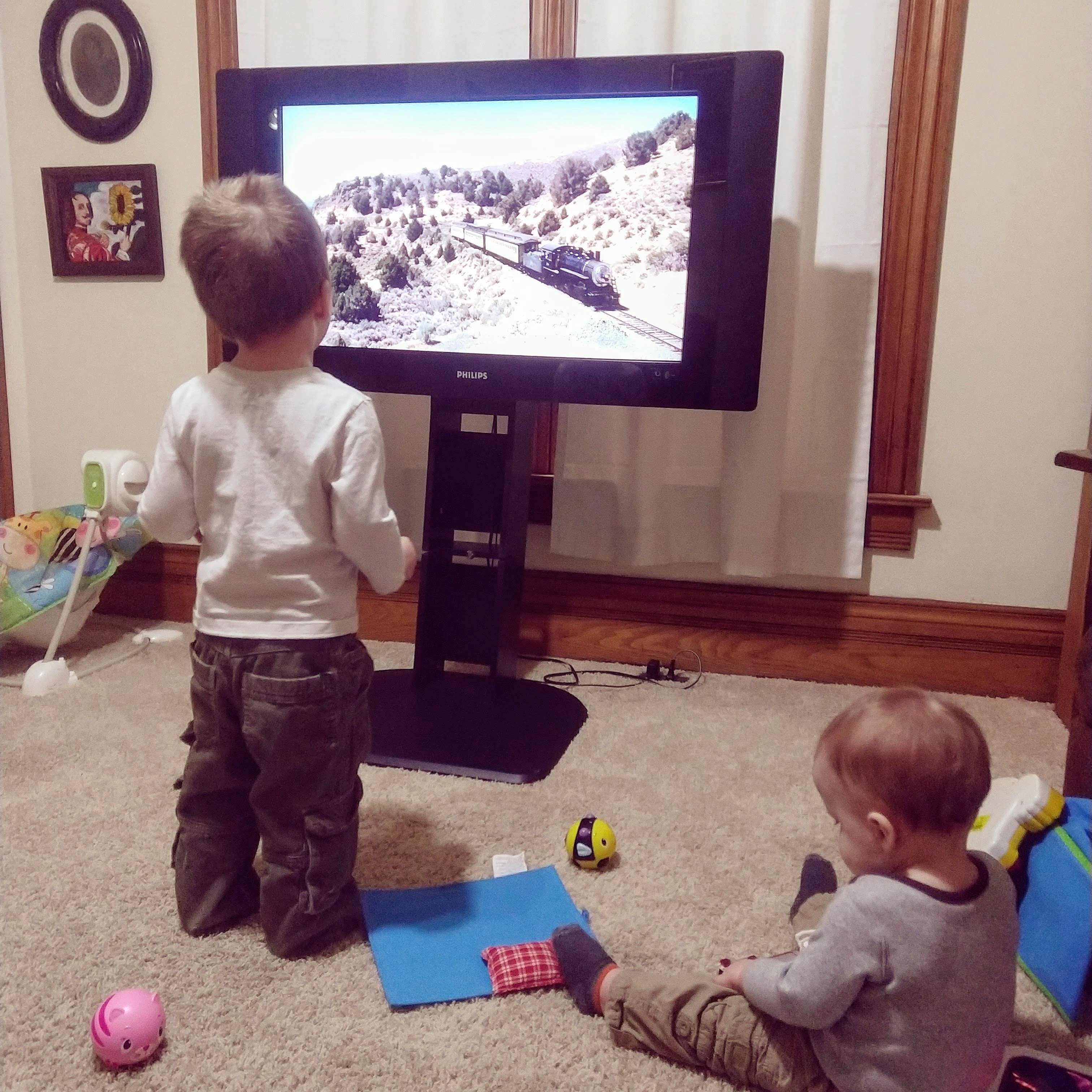 toddler and baby watching trains on tv