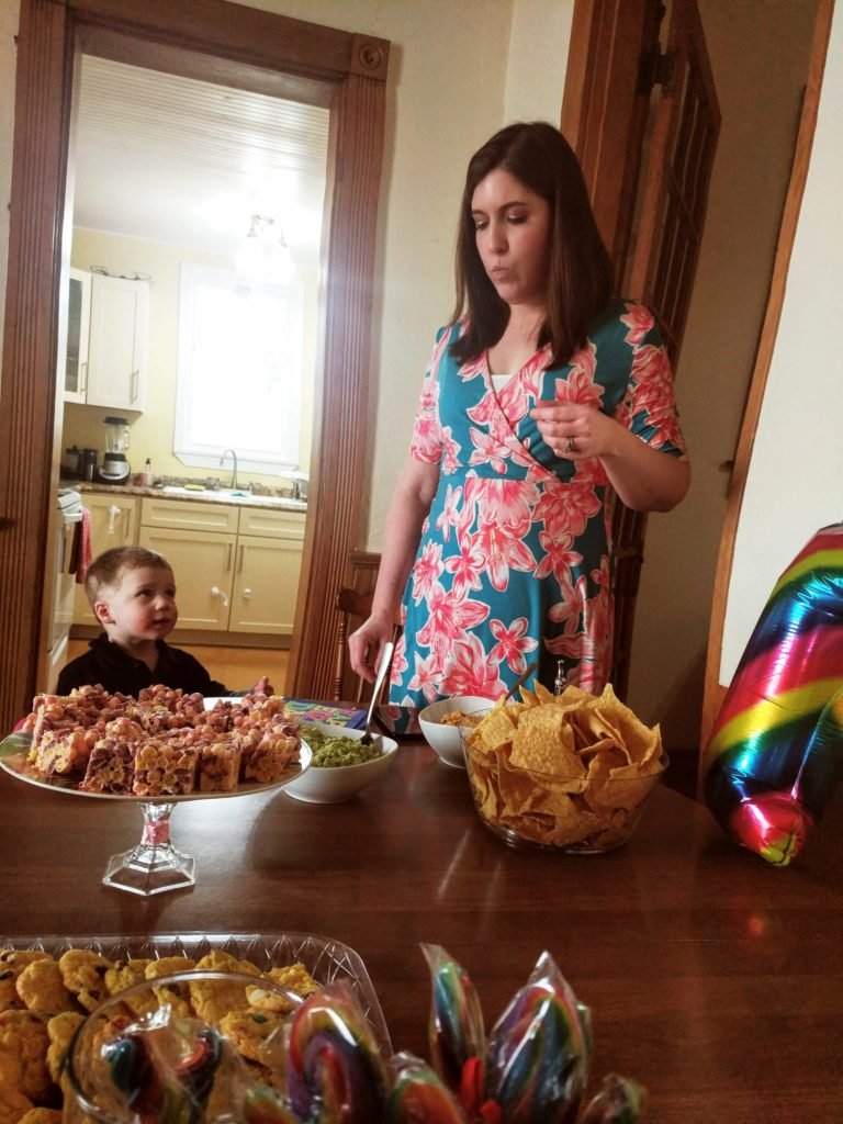toddler looking at woman aghast while she eats chips
