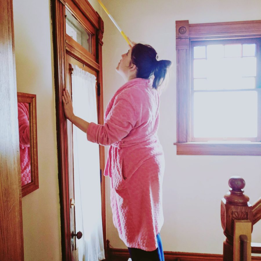woman in pink bathrobe on ladder cleaning woodwork in home
