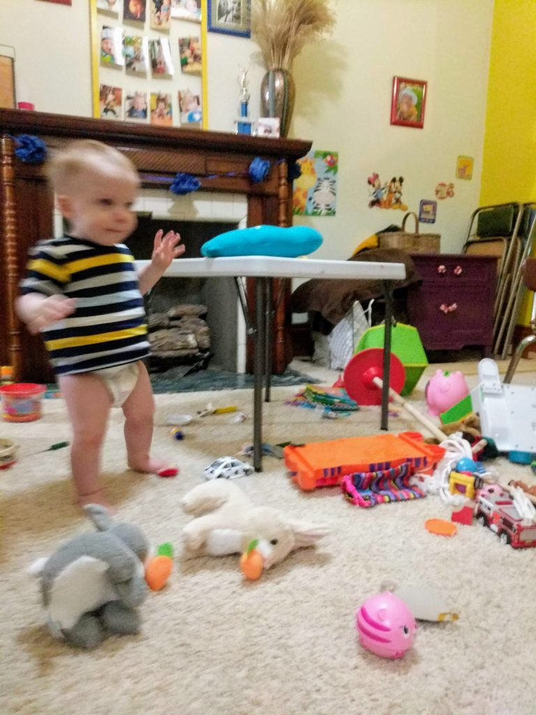 baby in a diaper looking at messy playroom