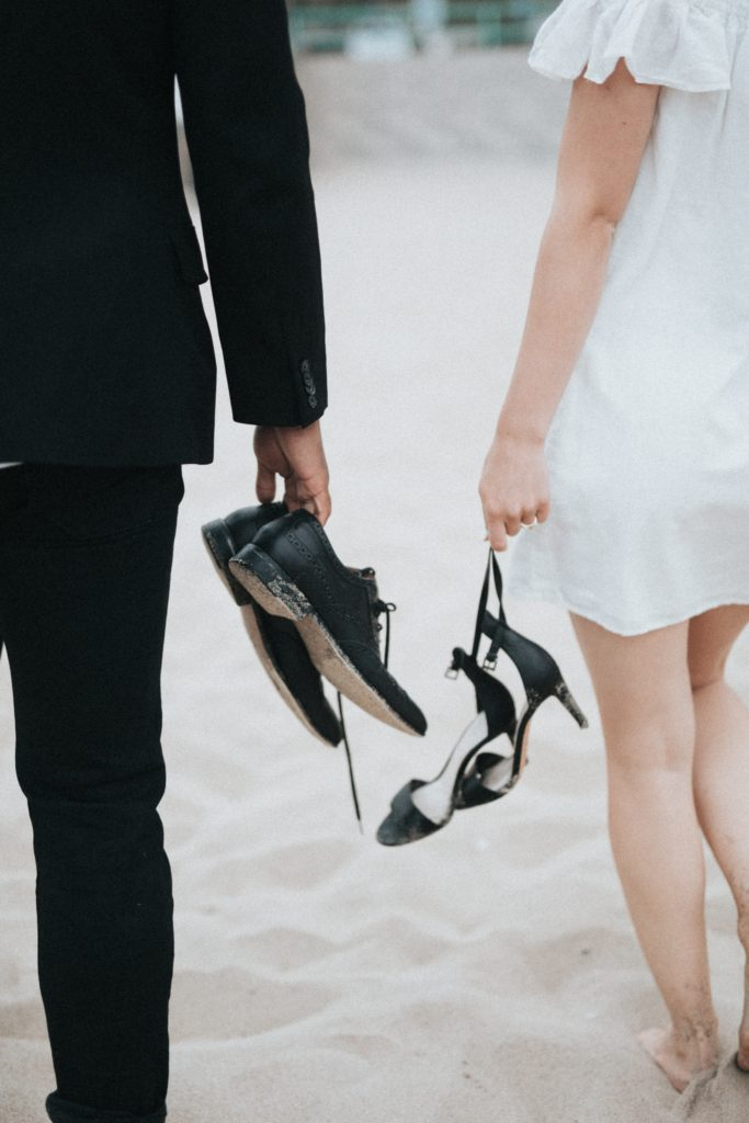 bride and groom walking away from camera, holding their shoes