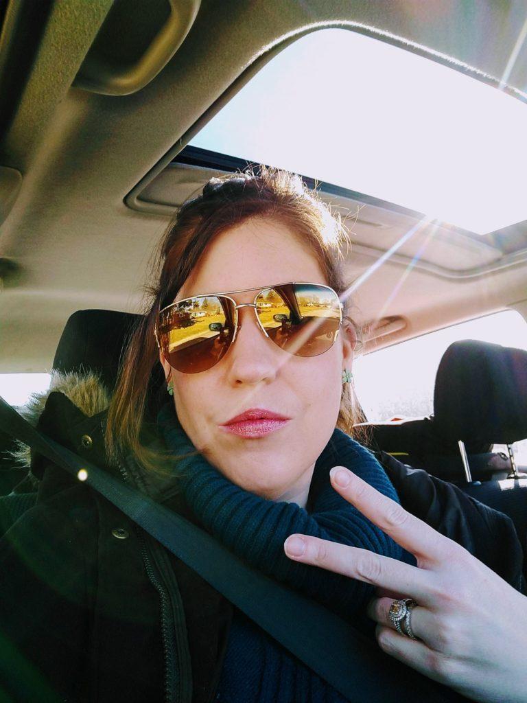 woman shpwing deuces to camera wearing sunglasses