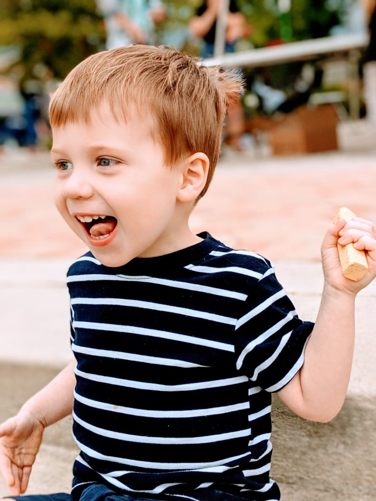 Autistic toddler smiling with piece of sidewalk chalk