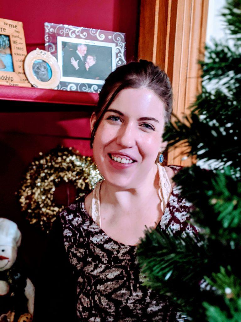 Megan smiling at the camera while decorating a Christmas tree
