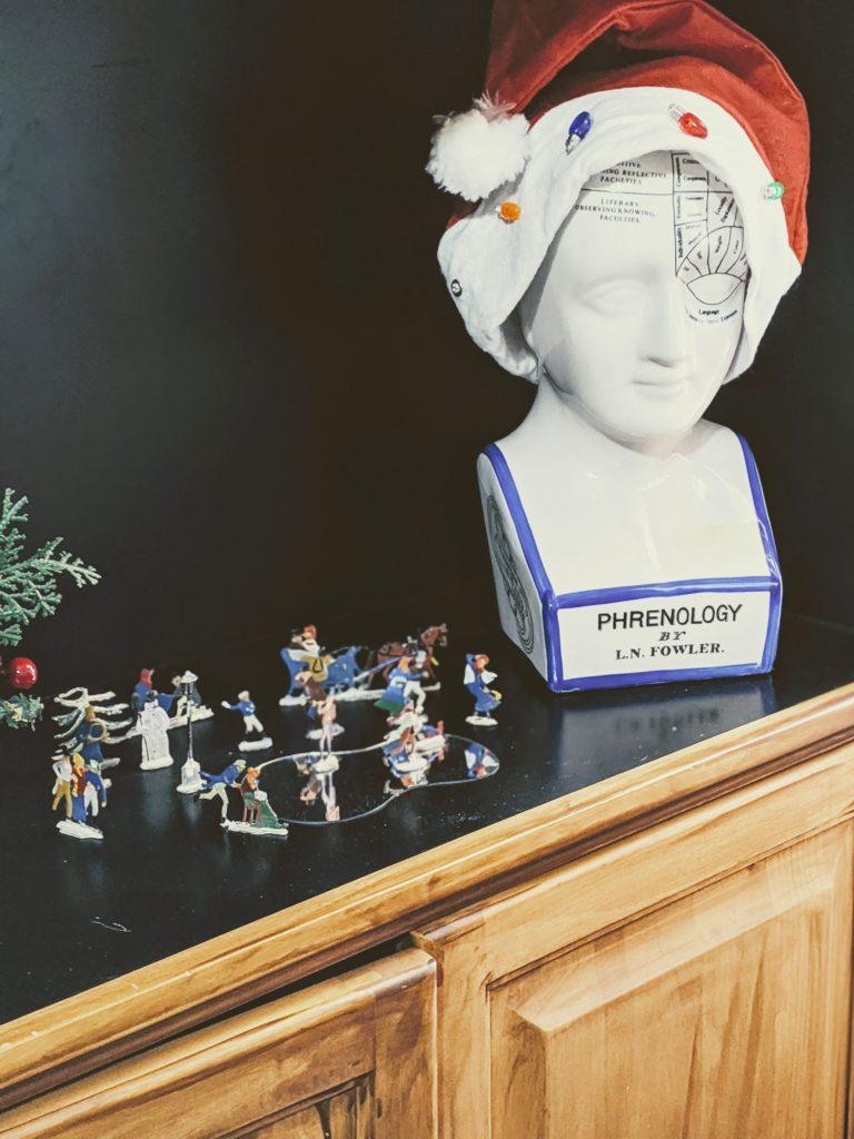 phrenology head wearing a santa hat and hans heinrichsen lead flats winter skating scene on shelf