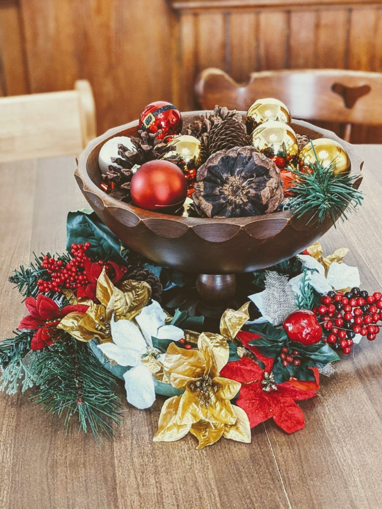 elevated farm house style wooden bowl filled with pine cones and christmas ornaments