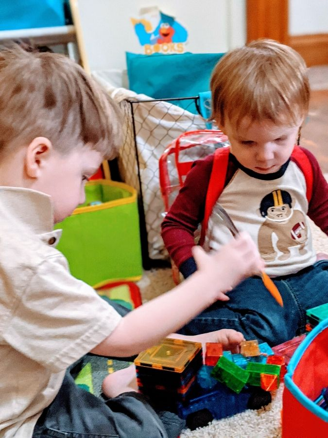 toddlers increasing hand strength by using tongs to pick up blocks