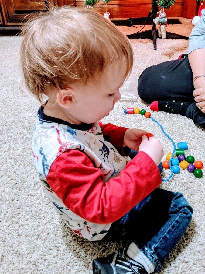 toddler threading beads onto string to increase fine motor skills
