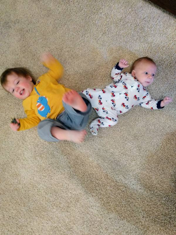 toddler and newborn baby laying on the floor