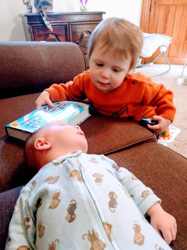 toddler offering newborn a book