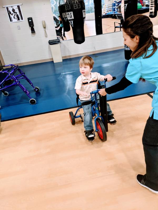 autistic boy riding bike at occupational therapy