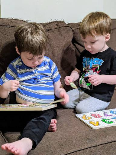 nonverbal child doing puzzle with sibling