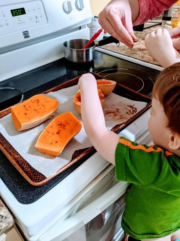 toddler helping cook squash