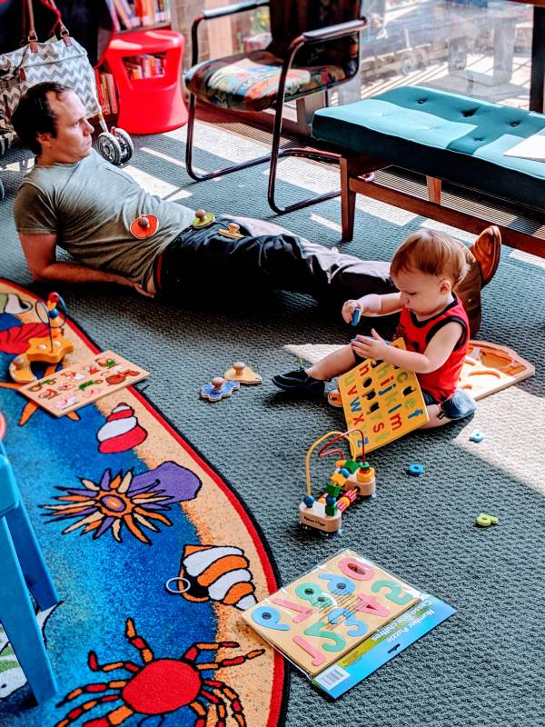 Father and toddler laying on floor of children's section in Morrisson Reeves Library in Richmond Indiana