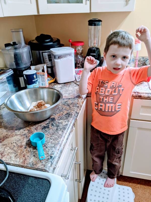 autistic boy helping family make dinner Why Should Kids Do Chores?