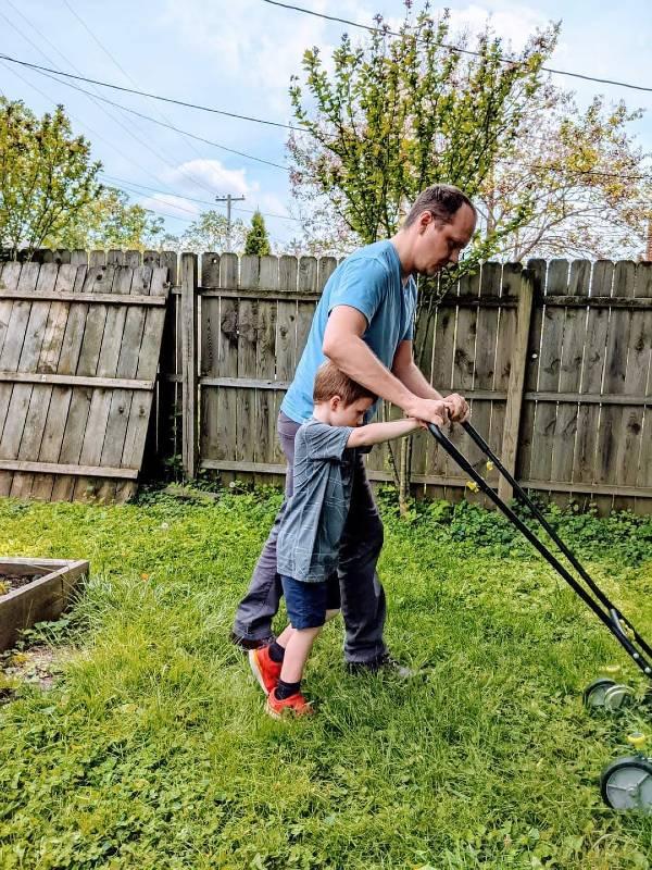 autistic boy helping dad with yard chores