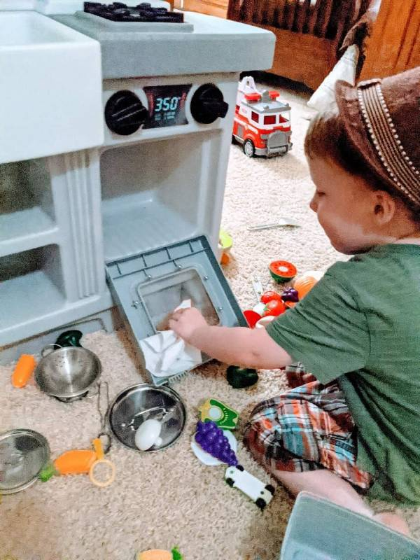 toddler cleaning his play oven
