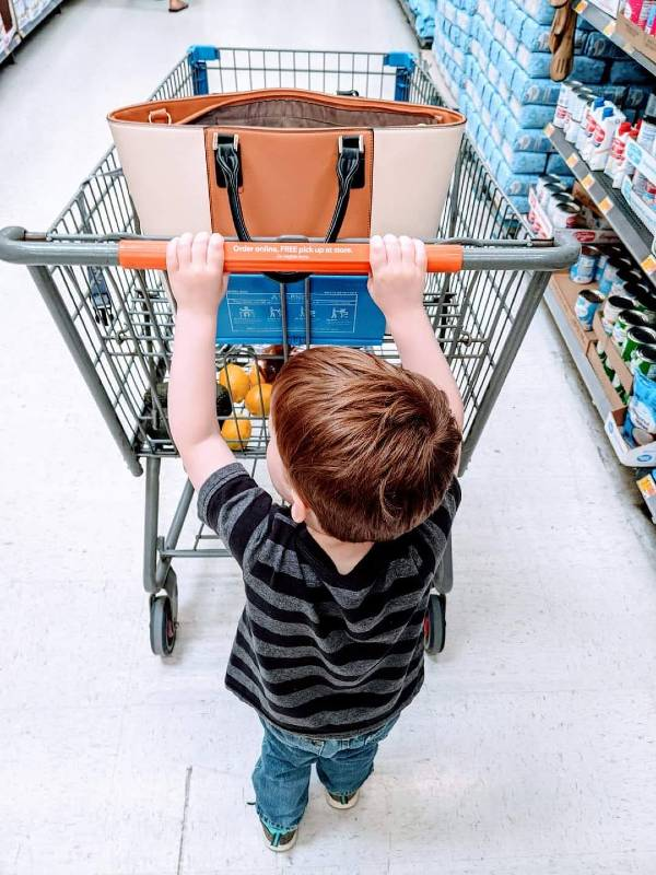 toddler boy helping push the shopping cart while grocery shopping
